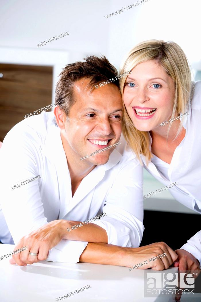 Stock Photo: Germany, Mid adult couple in kitchen, smiling.