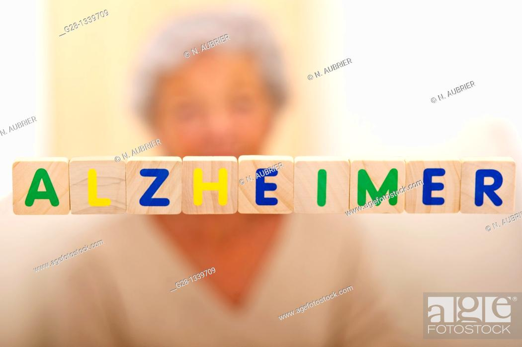 Stock Photo: Alzheimer written in bright letters and behind, blurred the silhouette of a senior woman.