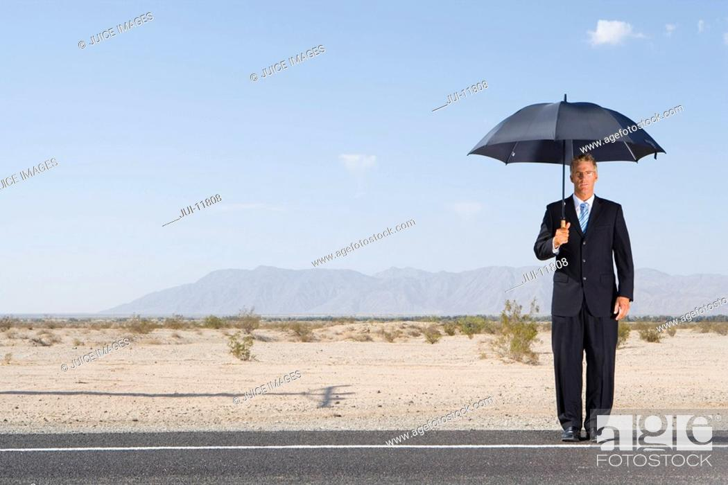 Stock Photo: Businessman with umbrella on open road in desert, portrait, low angle view.