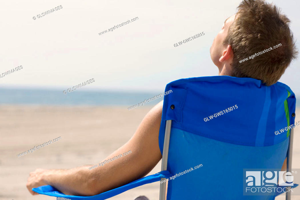 Stock Photo: Rear view of a young man sitting on the beach.