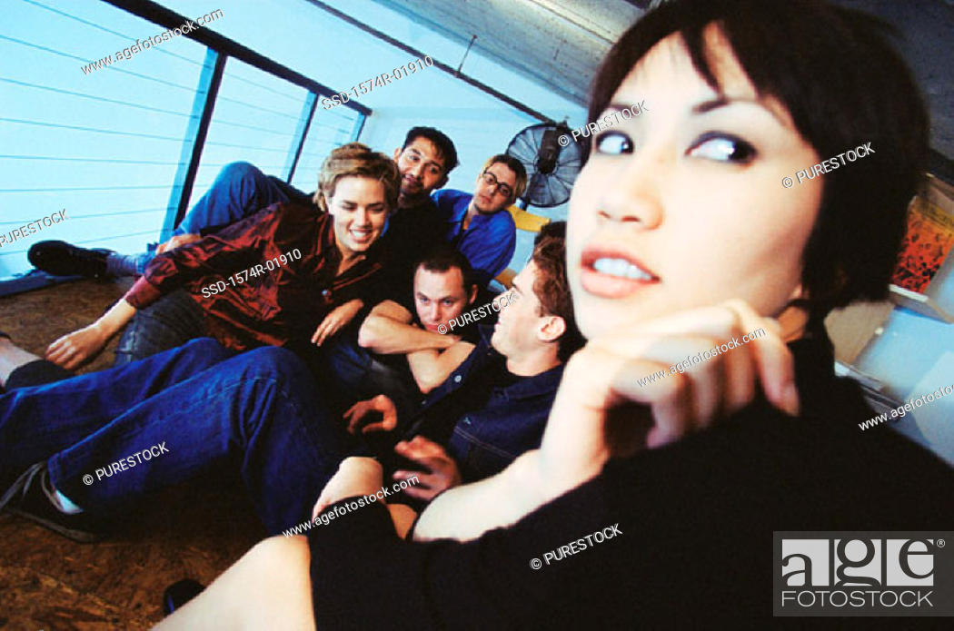 Stock Photo: Group of young men and women sitting indoors.