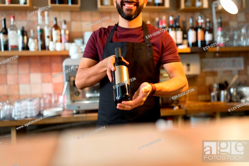 Stock Photo: small business, alcohol, people and service concept - happy man or bartender with bottle of wine at restaurant bar.