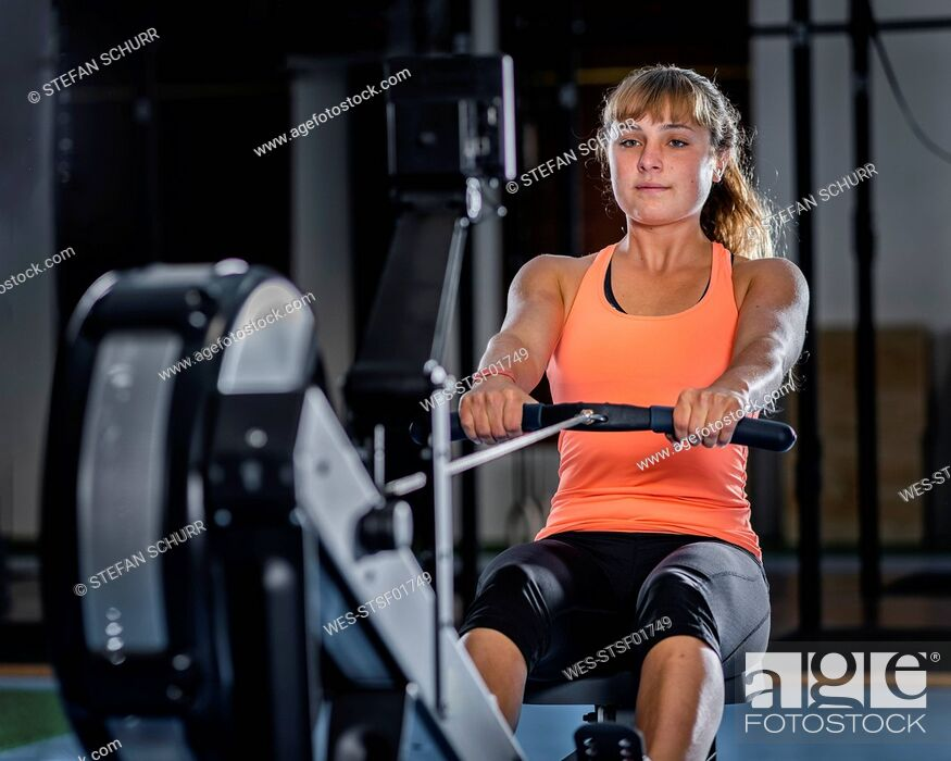 Stock Photo: Athletic young woman exercising with rowing machine at gym.