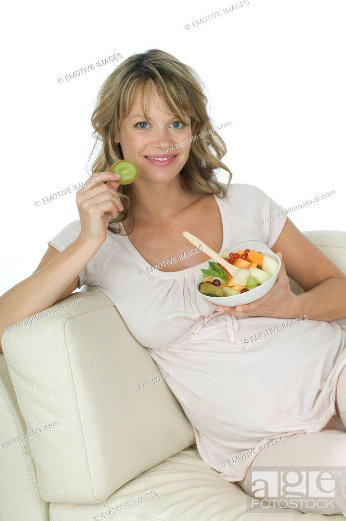 Stock Photo: Pregnant woman eating fruit salad.