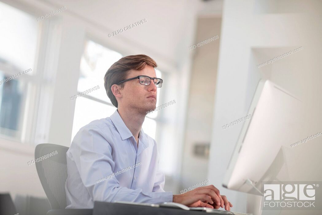 Stock Photo: Young male office worker typing at desktop computer.
