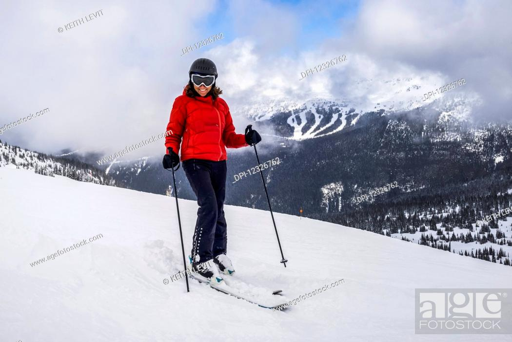 Photo de stock: A female downhill skier poses for the camera on a ski hill at a ski resort; Whistler, British Columbia, Canada.