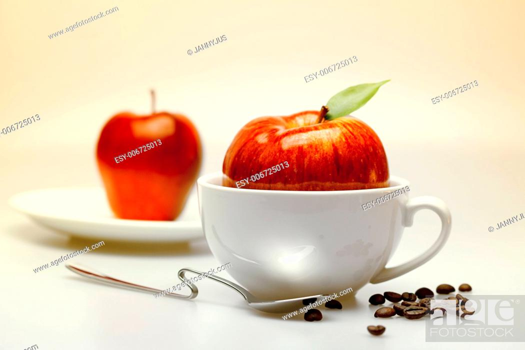 Imagen: apple in a cup, saucer, spoon and coffee beans.