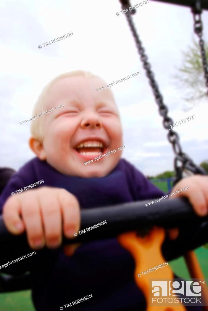 Stock Photo: 3 year boy sitting in swing laughing with joy.