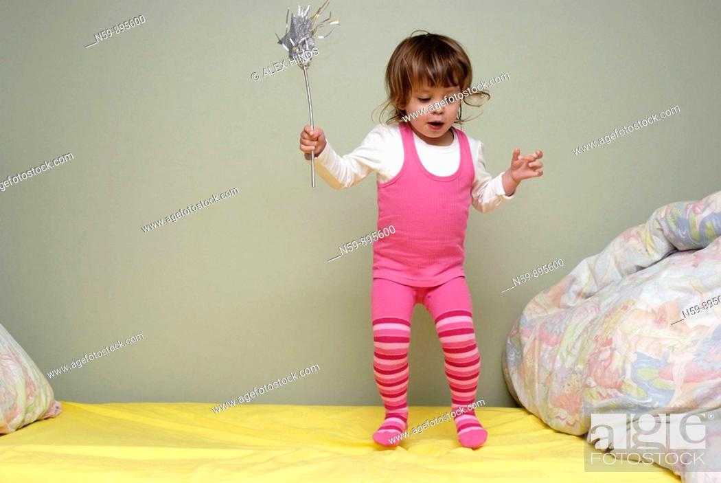 Stock Photo: Young girl, two and half years old, bouncing on her bed with a fairy wand.