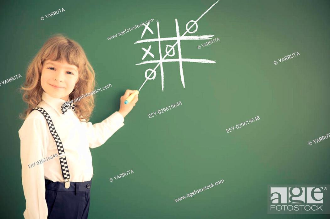 Stock Photo: School kid in class. Happy child against green blackboard. Education concept.