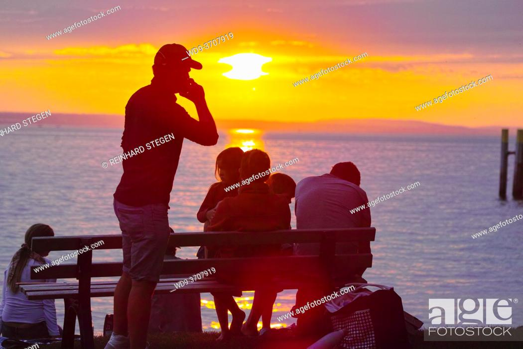 Stock Photo: business call while relaxing with family by a lake and sun is setting.