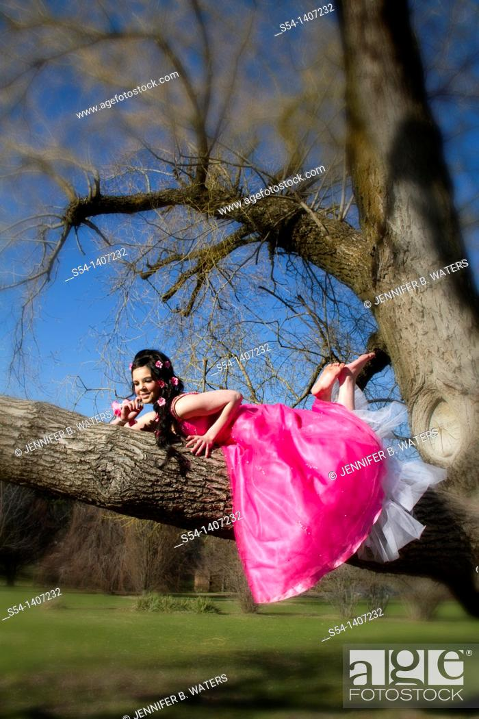 Stock Photo: A young woman in a pink dress, laying in a tree.