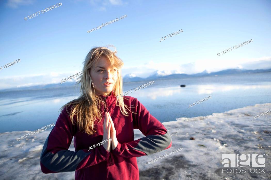 Stock Photo: Woman an icy beach before a run on the Homer beach, Kenai Peninsula, Southcentral Alaska.