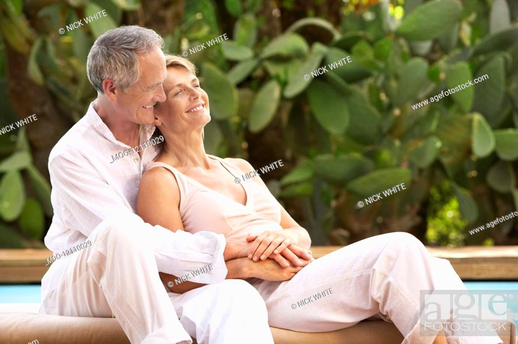 Stock Photo: Middle-aged couple sitting outdoors cuddling by pool.
