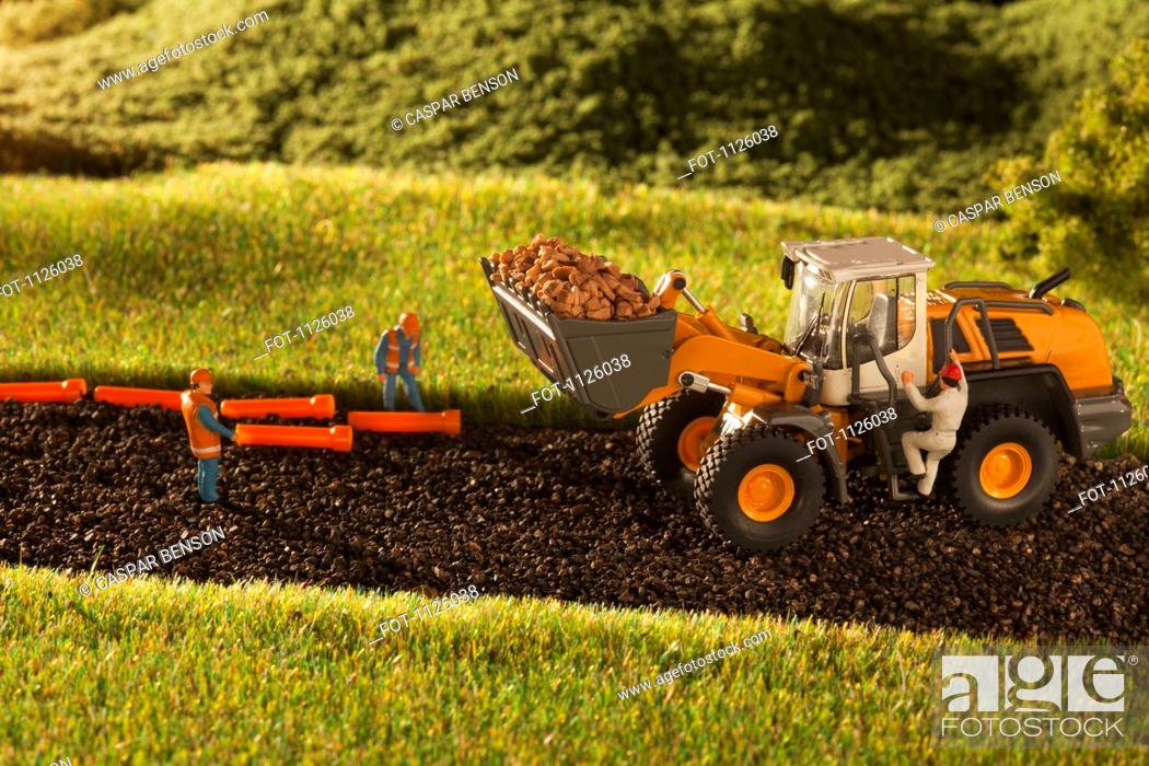 Stock Photo: A diorama of miniature construction workers and a bulldozer.