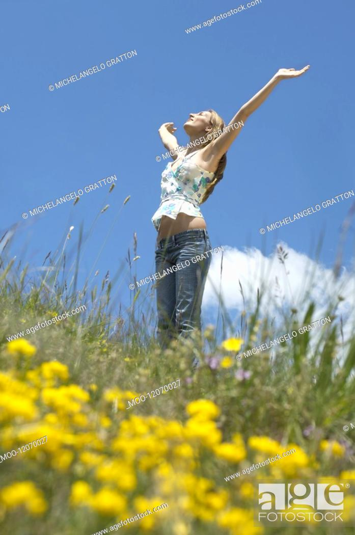 Stock Photo: Young woman standing in field with open arms low angle view side view.