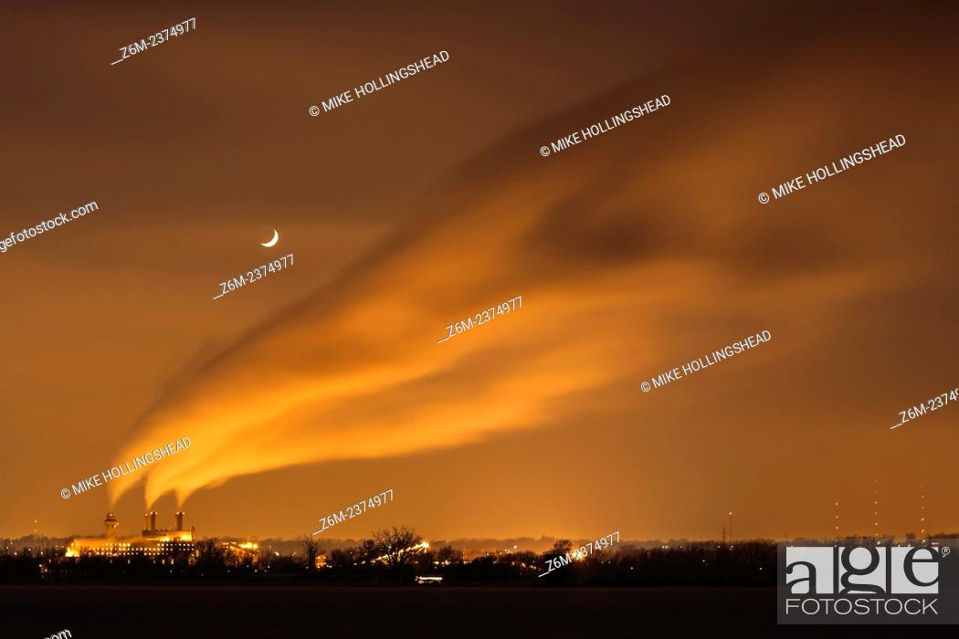 Stock Photo: Crescent moon shines above wind blown plant steam in north Omaha.