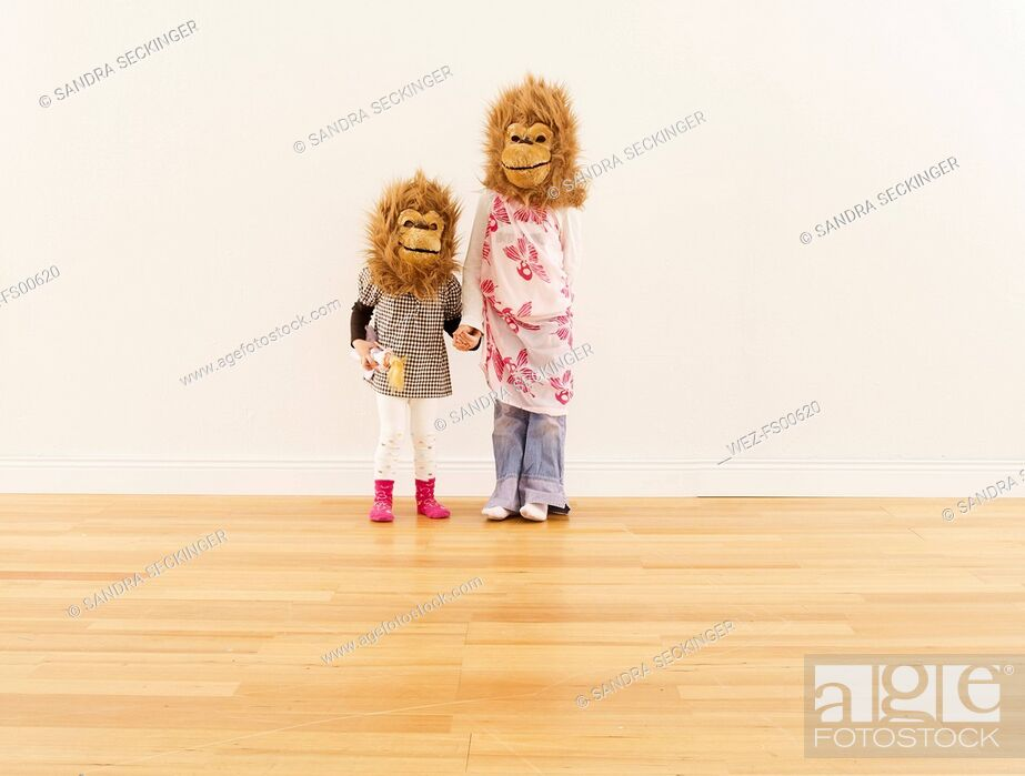 Stock Photo: Two girls wearing monkey masks standing hand in hand in front of white wall.