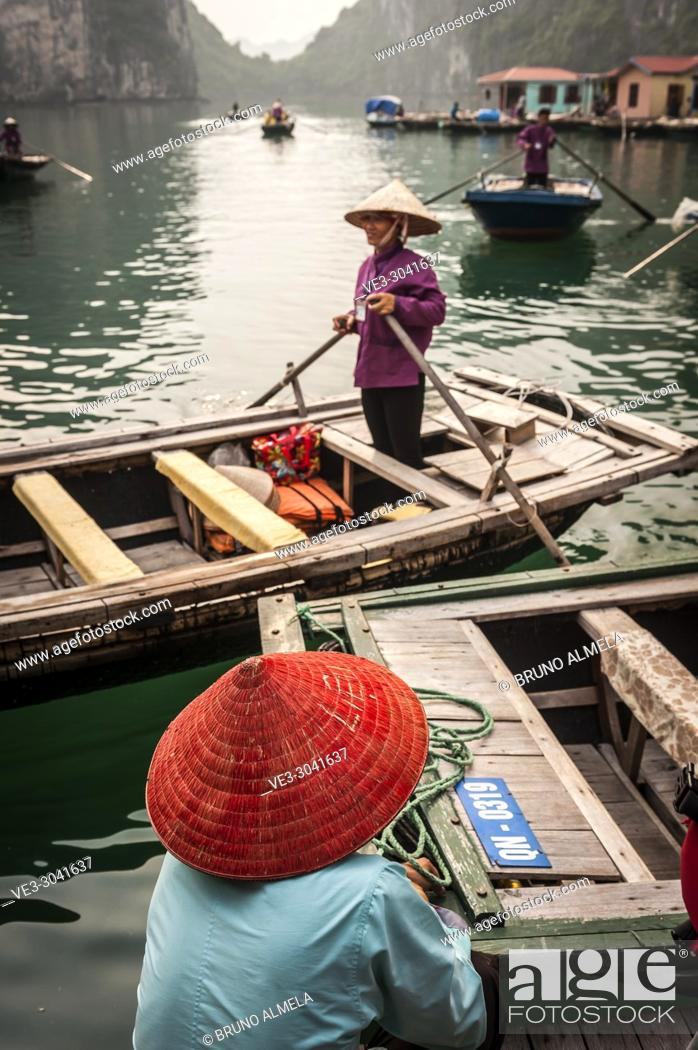 Stock Photo: Vietnamese boat woman in the karst landscape of Ha Long Bay, Quang Ninh Province, Vietnam. Ha Long Bay is a UNESCO World Heritage Site.