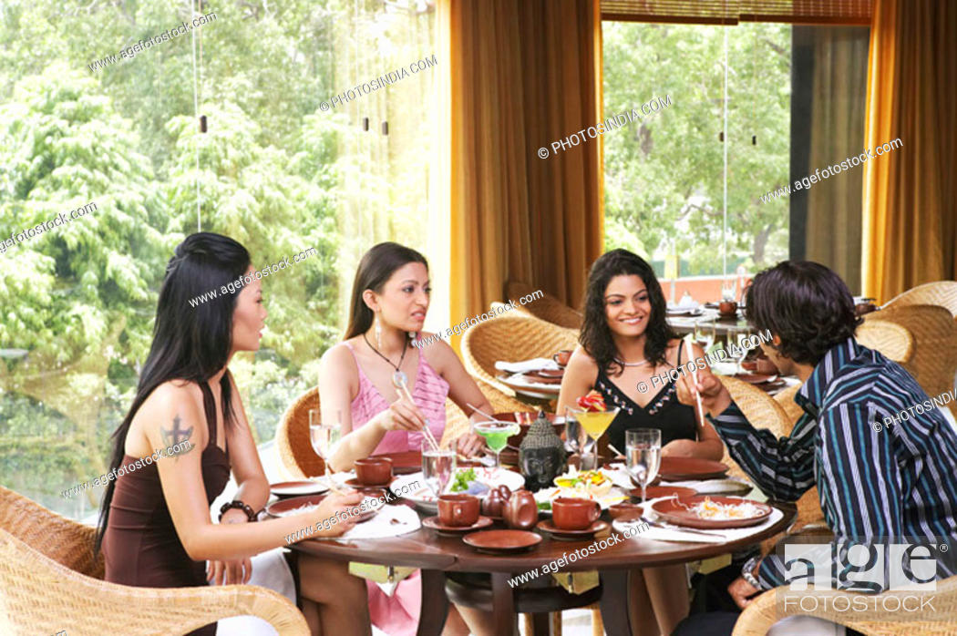 Stock Photo: Three young women and a young man dining in a restaurant.