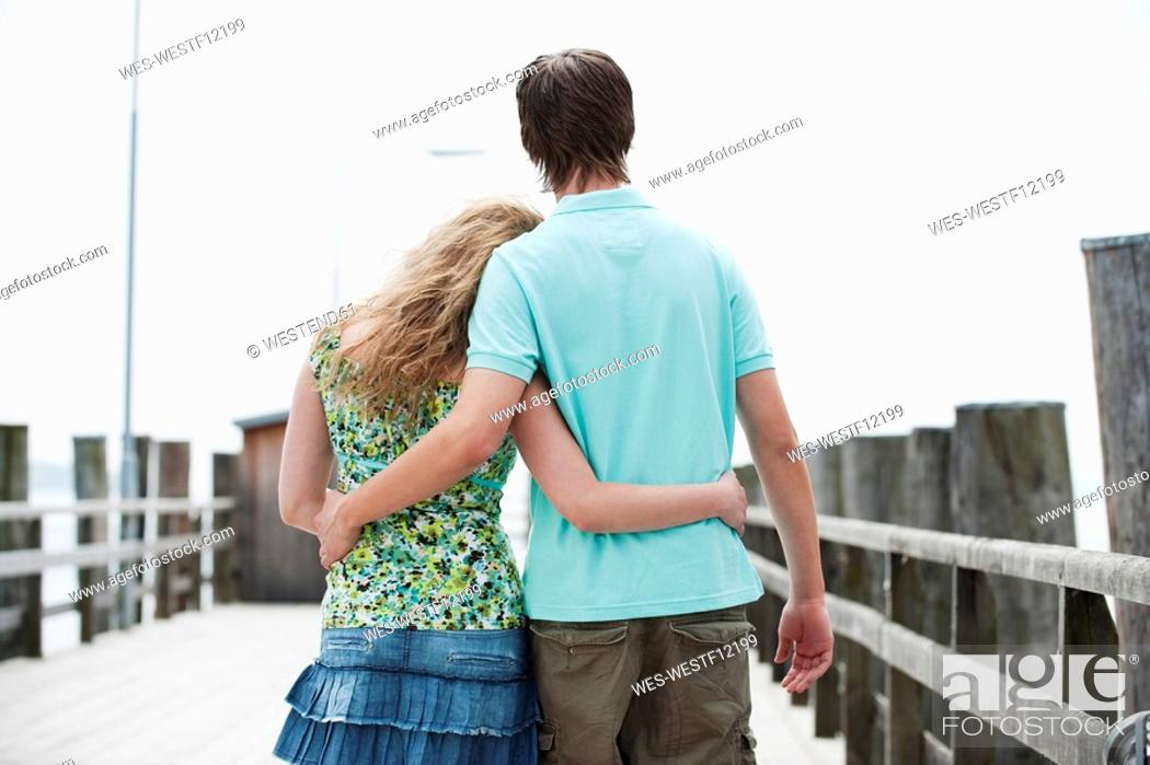 Stock Photo: Germany, Bavaria, Ammersee, Couple walking across pier, rear view.