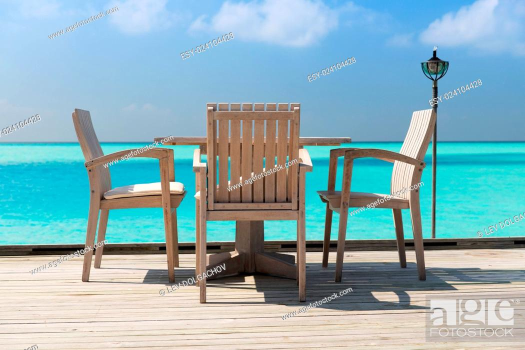 Stock Photo: travel, tourism, vacation and summer holidays concept - outdoor restaurant wooden terrace with table and chairs over sea background.