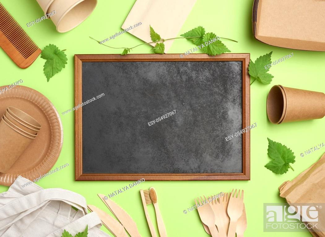 Stock Photo: empty wooden frame and disposable paper plates, cups, wooden forks on green background. View from above, plastic rejection concept, zero waste.