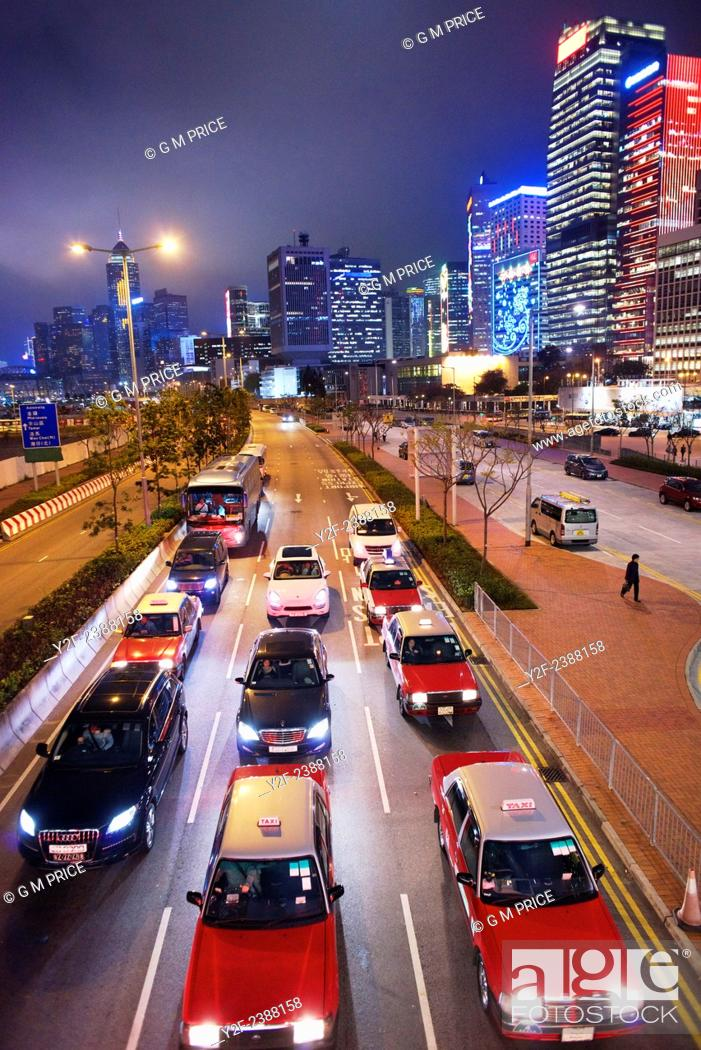 Imagen: cars wait at traffic lights with Hong Kong skyline in the background.