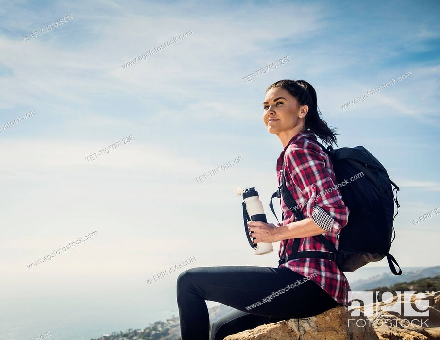 Stock Photo: Woman with water bottle sitting on rock.