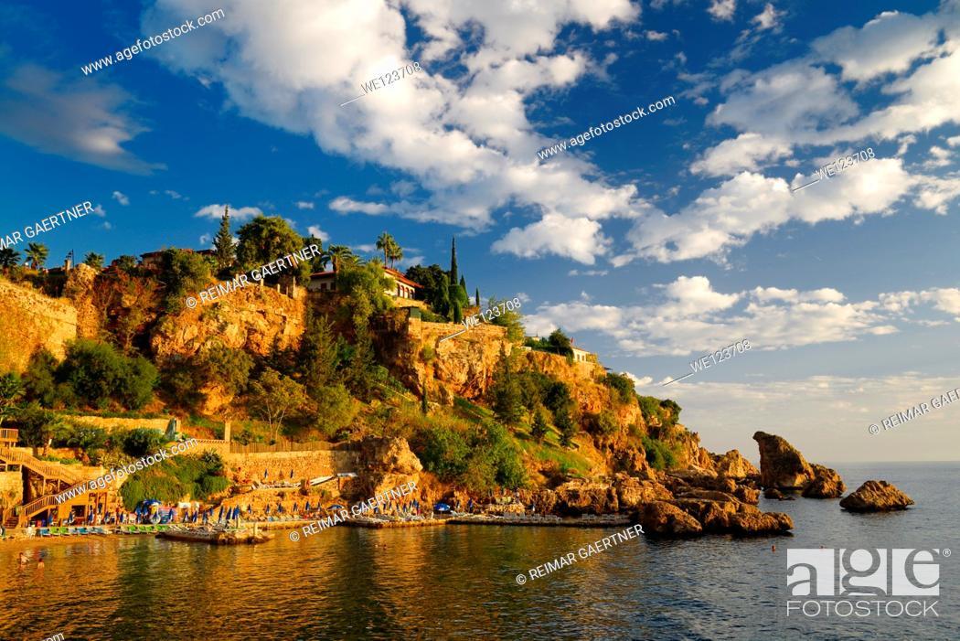 Stock Photo: Cliffside resort and beach on Turkish Riviera at Antalya Kaleici Harbour Turkey at sunset.