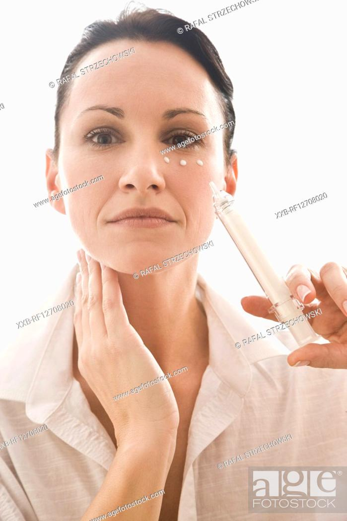 Stock Photo: woman applying eye cream.
