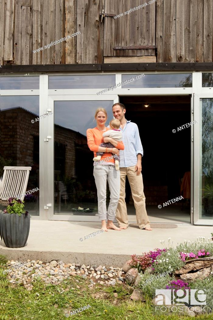 Stock Photo: A woman and man and their baby standing in front of their house.