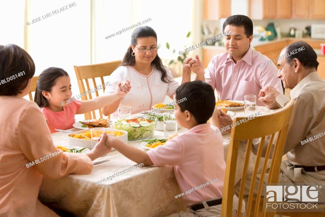 Stock Photo: Hispanic family praying at dinner table.