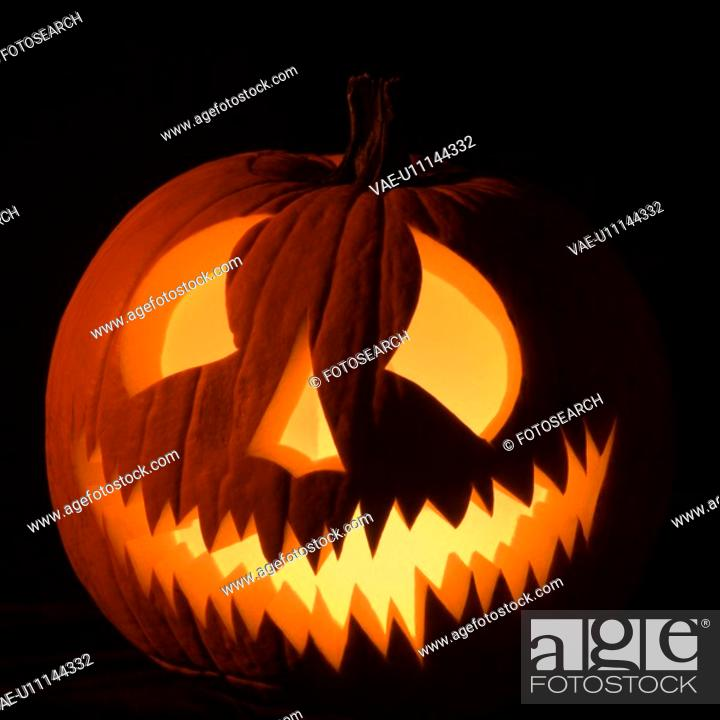 Stock Photo: Carved Halloween pumpkin glowing in the dark.
