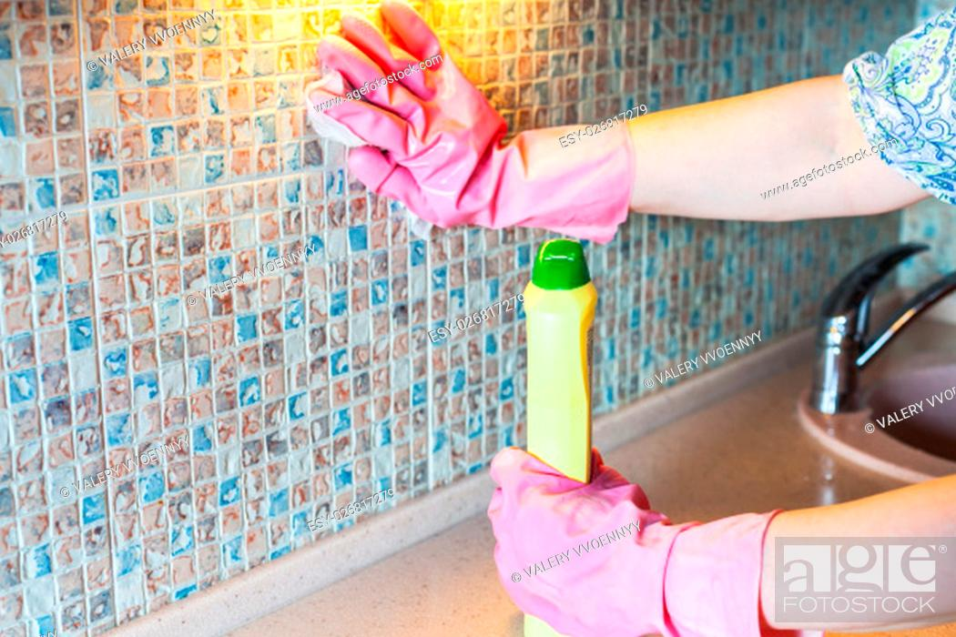 Stock Photo: House cleaning - woman washes ceramic tiles on kitchen wall with detergent.