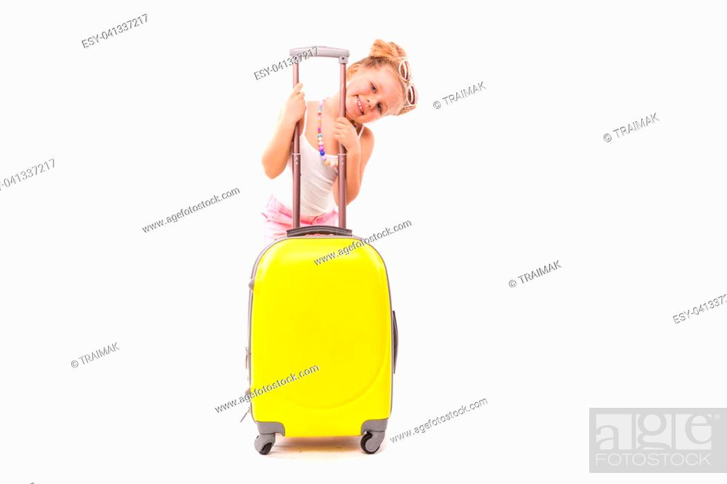 Stock Photo: Isolated on white, attractive young caucasian blonde girl in white shirt, pink shorts, sunglasses and sandals stand near the yellow suicase.