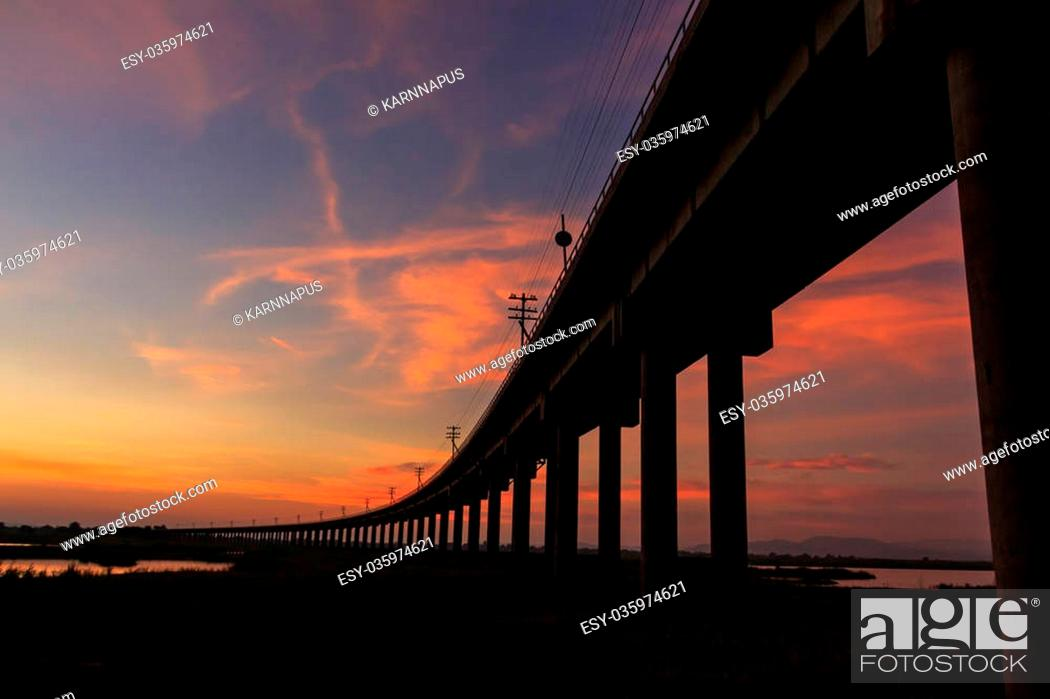 Stock Photo: A train bridge at Pa Sak Jolasid Dam, Thailand in sunset time.