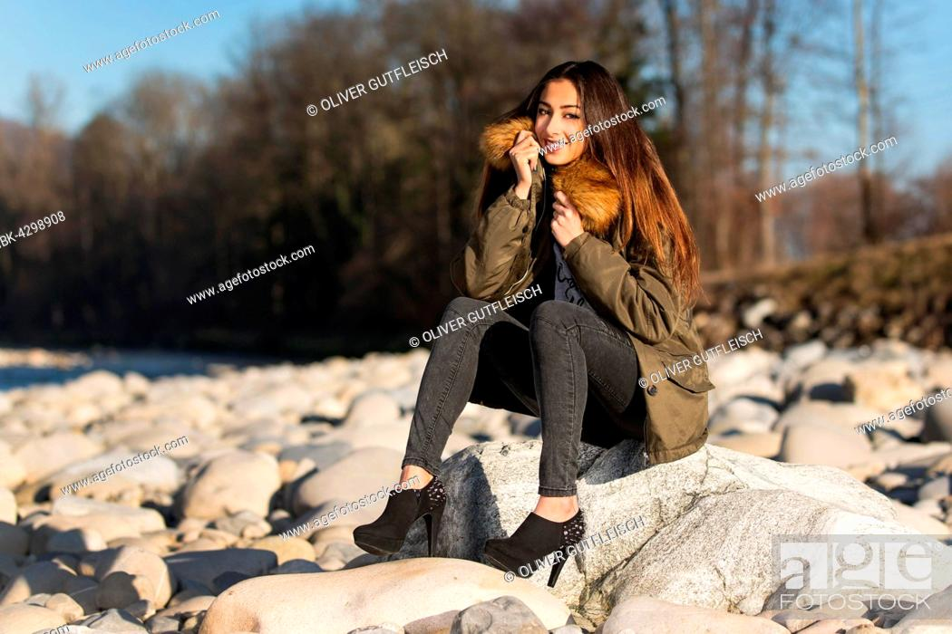 Imagen: Young woman with long brunette hair sits on stone in dry river in winter, fashion, look into the camera.