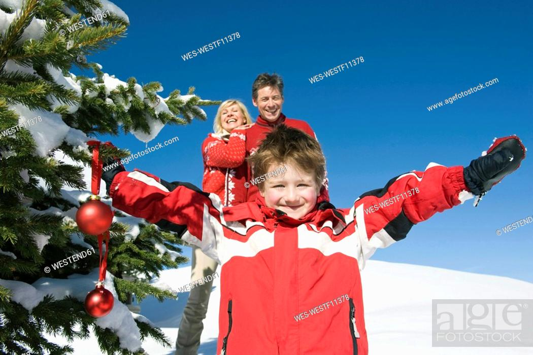 Stock Photo: Italy, South Tyrol, Seiseralm, Boy 4-5 holding Christmas baubles, parents in background, portrait.