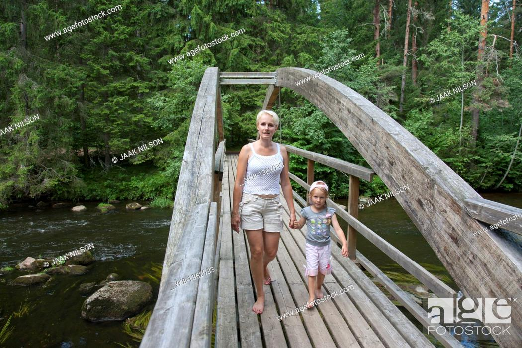 Stock Photo: Mother With Kid Walking Over Wooden Bridge Holding Hands, Põlva County, Estonia, Europe.