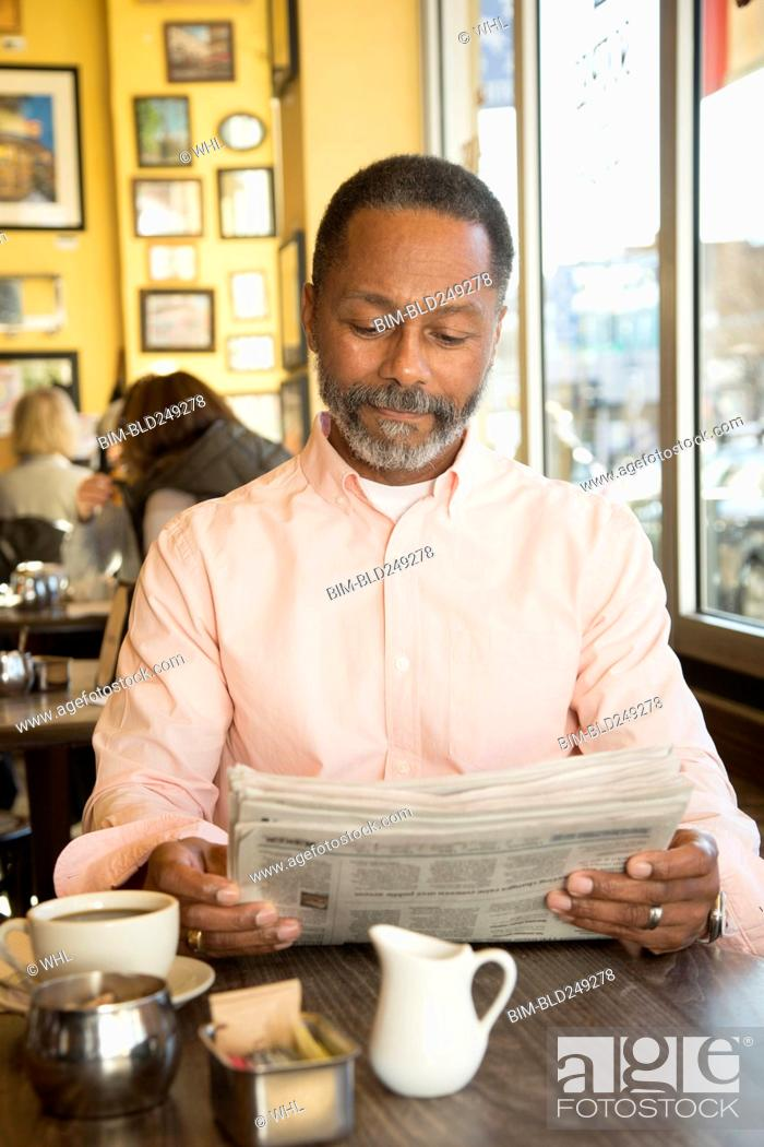 Stock Photo: Mixed Race man reading newspaper in coffee shop.