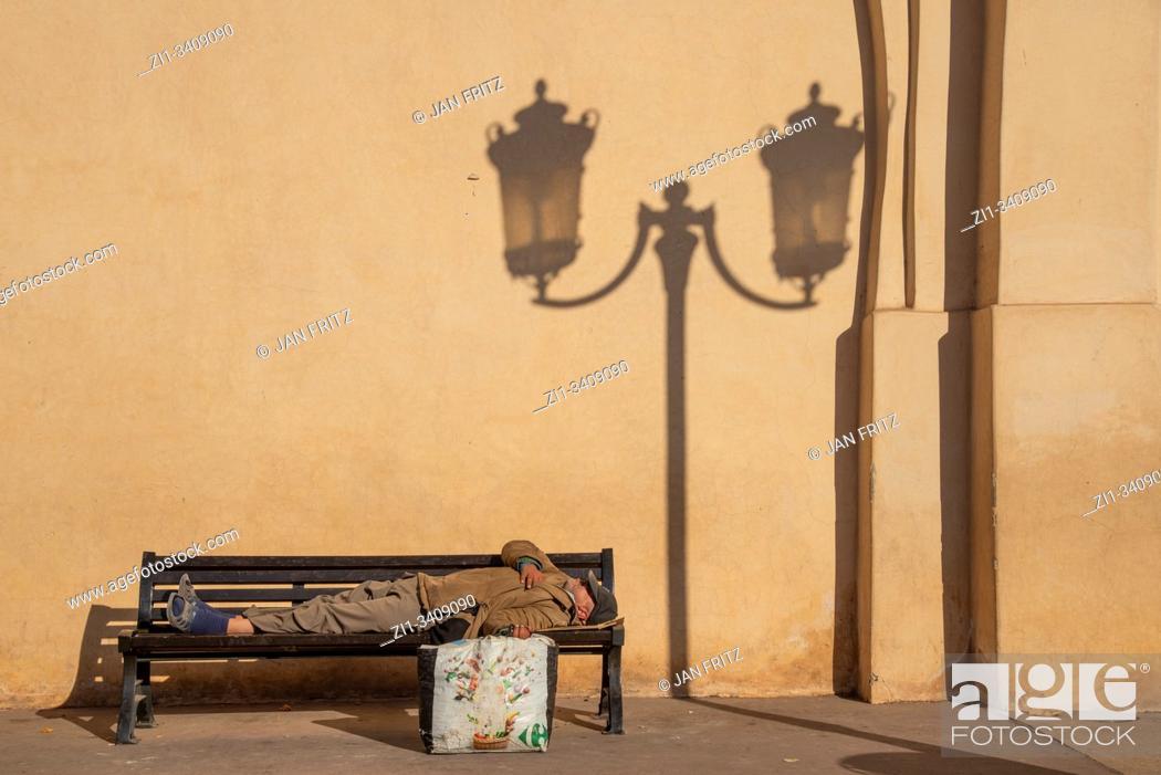 Imagen: poor man asleep at bench in Marrakech, Morocco.
