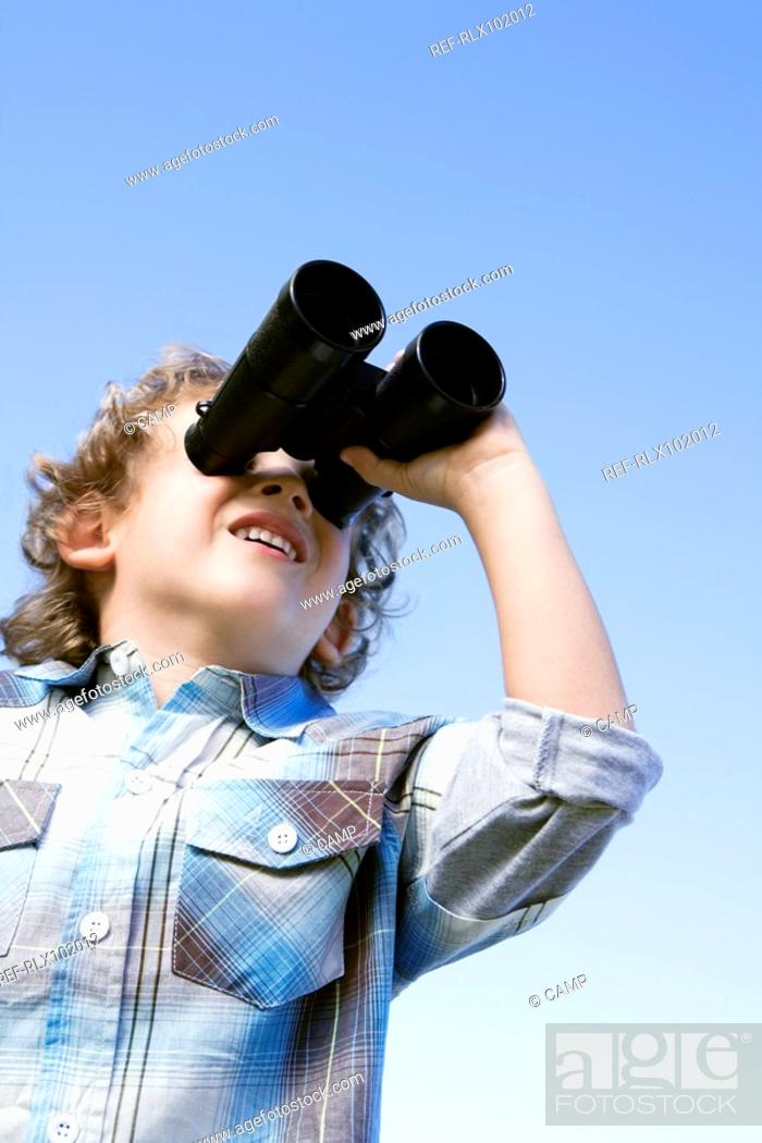 Stock Photo: Boy 4-7 standing outdoors using binoculars.