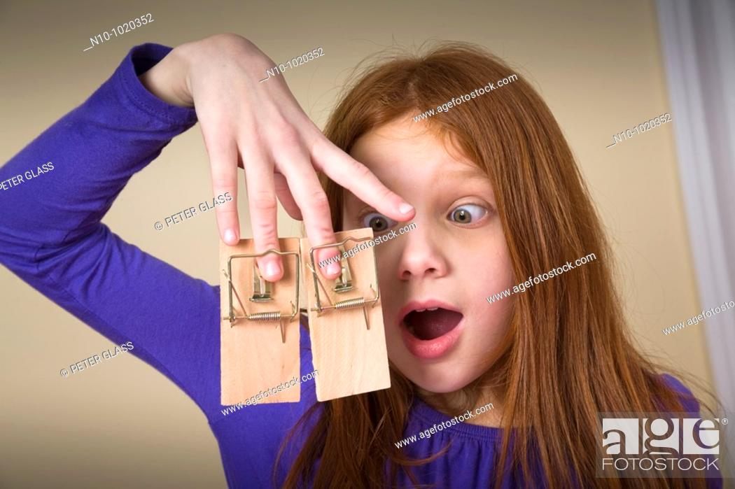 Stock Photo: Preteen redhead girl with mousetraps on her fingers.