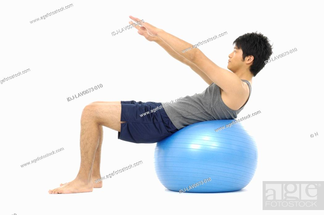 Stock Photo: Man doing exercise on exercise ball.