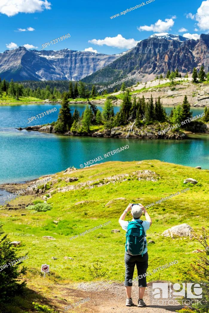 Stock Photo: Female hiker standing on a trail taking a photo with her phone of an alpine lake with mountains, blue sky and clouds; Banff, Alberta, Canada.