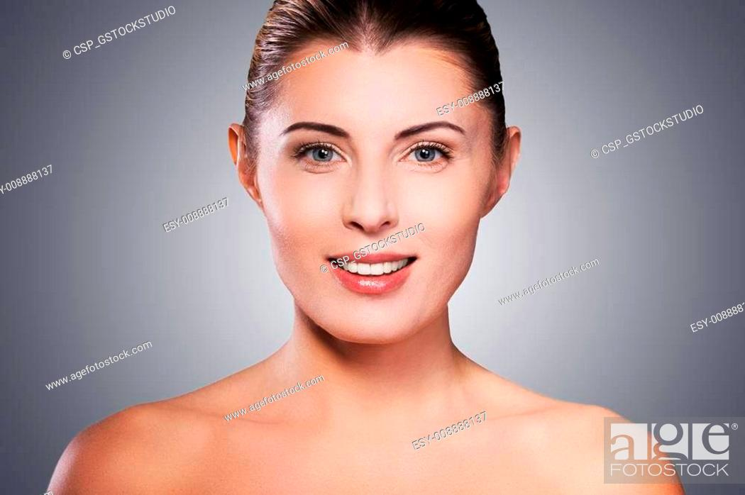 Stock Photo: Natural beauty. Portrait of shirtless mature woman smiling while standing against grey background.