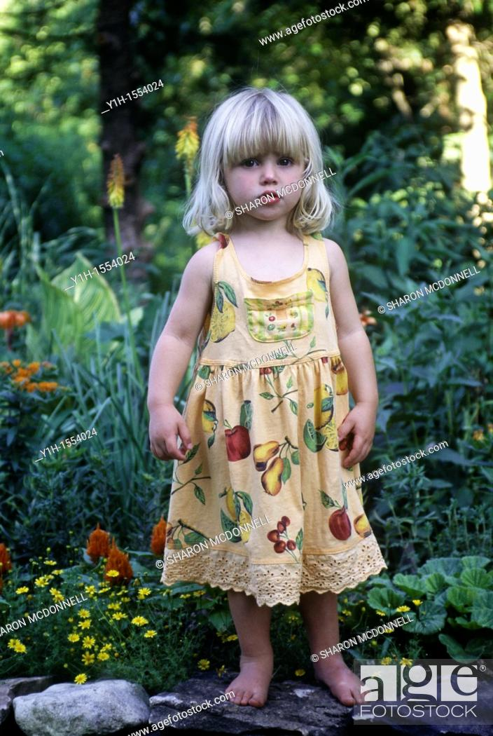 Stock Photo: Blonde young girl, 3-4 years old, standing on rock wall in garden on a summer morning.