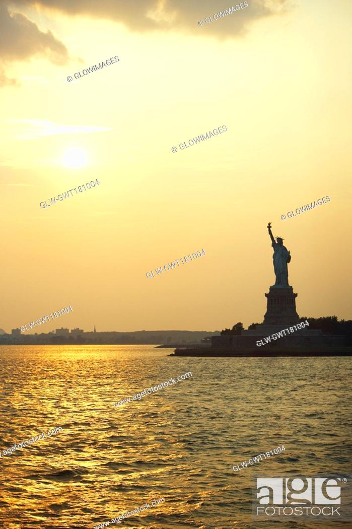 Stock Photo: Silhouette of a statue at dusk, Statue Of Liberty, New York City, New York State, USA.