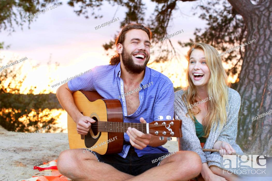 Imagen: Young couple playing guitar by lake.